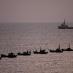 Fishing boats, leaving the fishing grounds in the South China Sea, pass an oil tanker on the way back to the harbor.